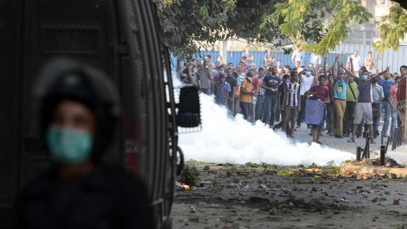 Egyptian protesters throw stones at riot police during clashes near the U.S. Embassy in Cairo on Thursday.