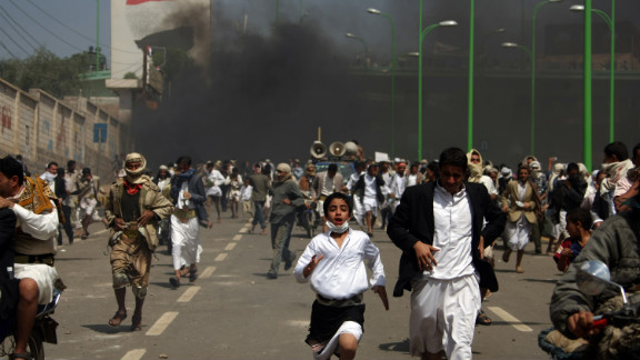 Yemeni protesters run for cover from tear gas fired by riot police in Sanaa on Friday.