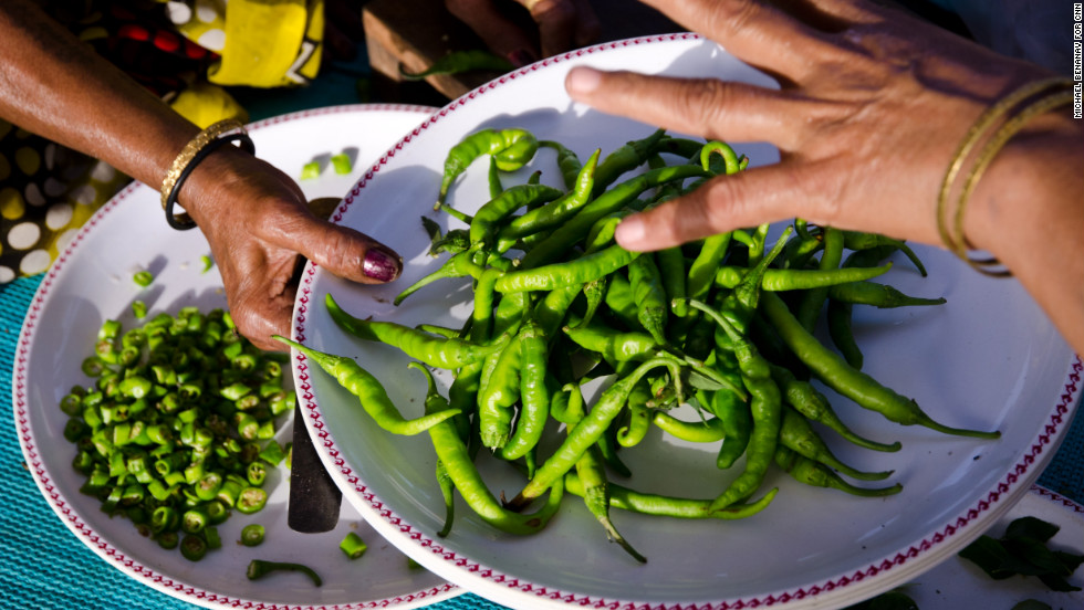 Hired cooks load up a plate with chili peppers. Traditionally, the bride's family members did all the cooking themselves. But today, families bring in help if they can afford it.