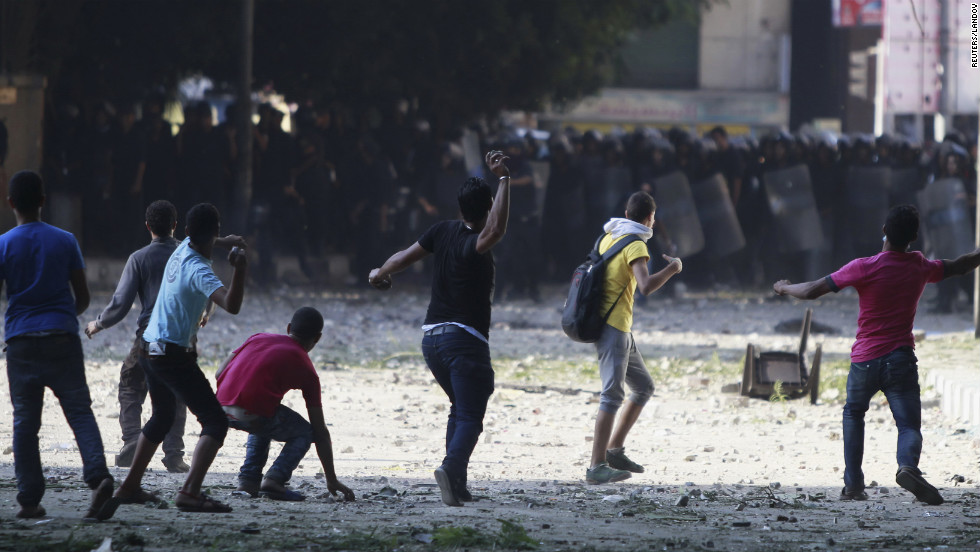 Protesters throw stones toward riot police during clashes along a road leading to the U.S. Embassy near Tahrir Square in Cairo on Friday, September 14.