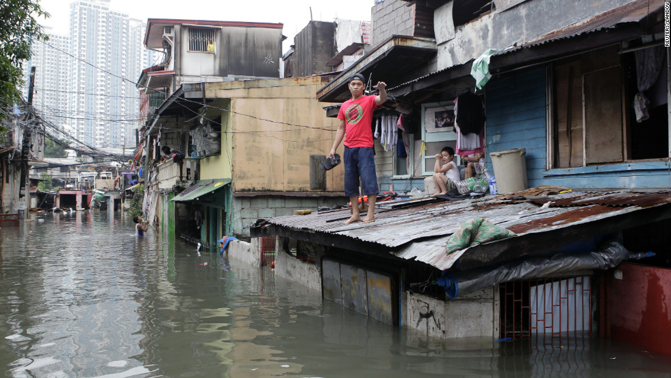 A man waits for a boat to transport him to higher ground on a flooded street after continuous overnight rain brought by Typhoon Sanba in San Juan, Philippines, on Saturday.