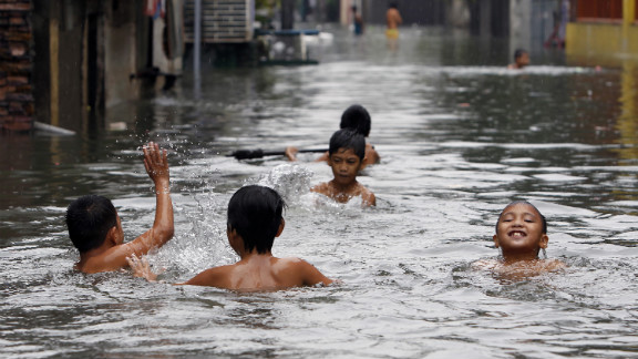 Children swim in water on a flooded street in San Juan, metro Manila on Saturday. See photos of last month's  flooding in Manila from monsoon rains.