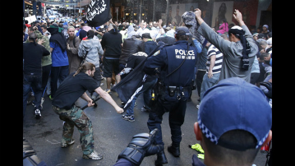 A protester hits a policeman with a pole in Sydney