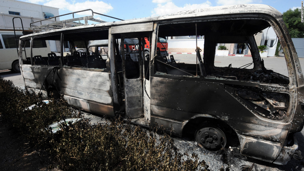 A burned bus sits in the grounds of the American school in Tunis on Saturday.