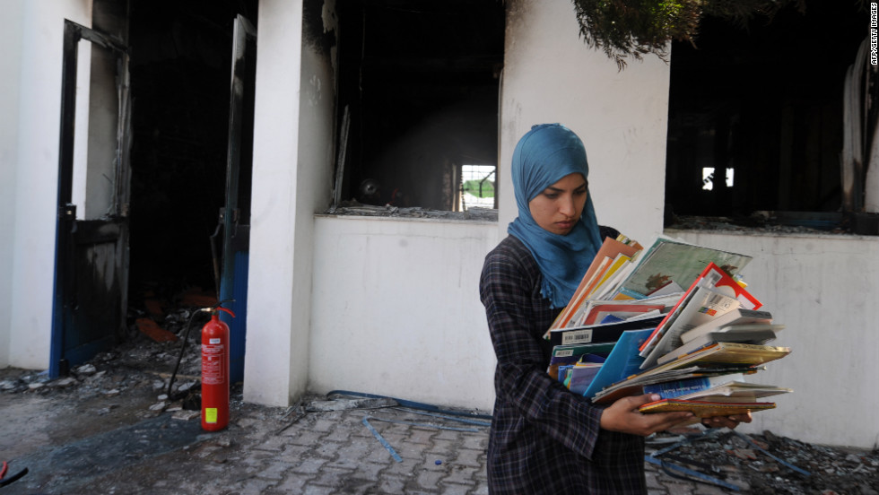 A  woman collects books from a classroom in the American school in Tunis on Saturday.