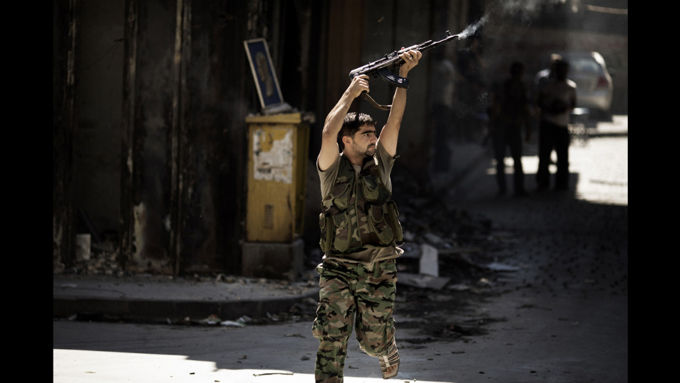 A Syrian rebel fires at a position held by regime forces during clashes on Friday in Aleppo.