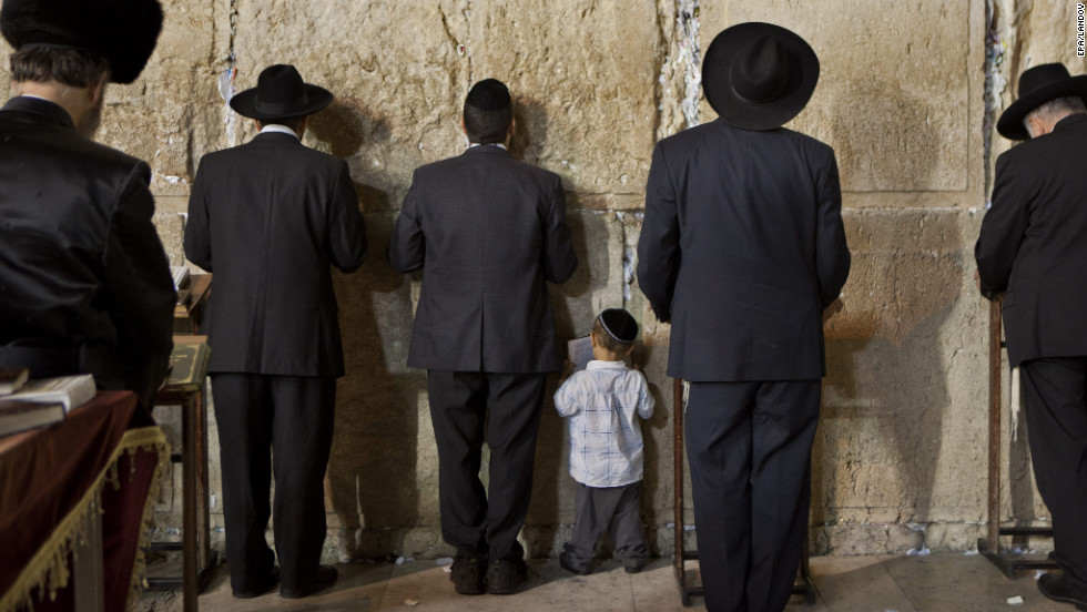 A young Jewish boy holds a prayer book as he follows his father to his left and others in prayer at the Western Wall.