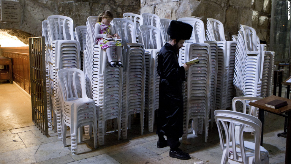 A girl sits on a stack of plastic chairs as her father reads from a prayer book and faces the Western Wall on the night of Saturday, September 8. Many Jews recited prayers for the beginning of a new week, which starts as Shabbat ends on sundown on Saturdays.