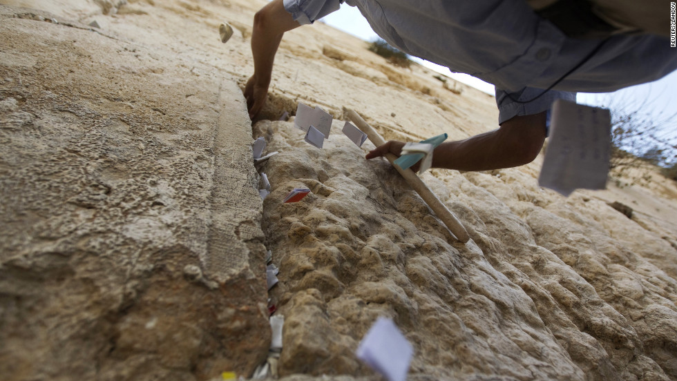 A worker removes notes from the cracks of the Western Wall on Monday.