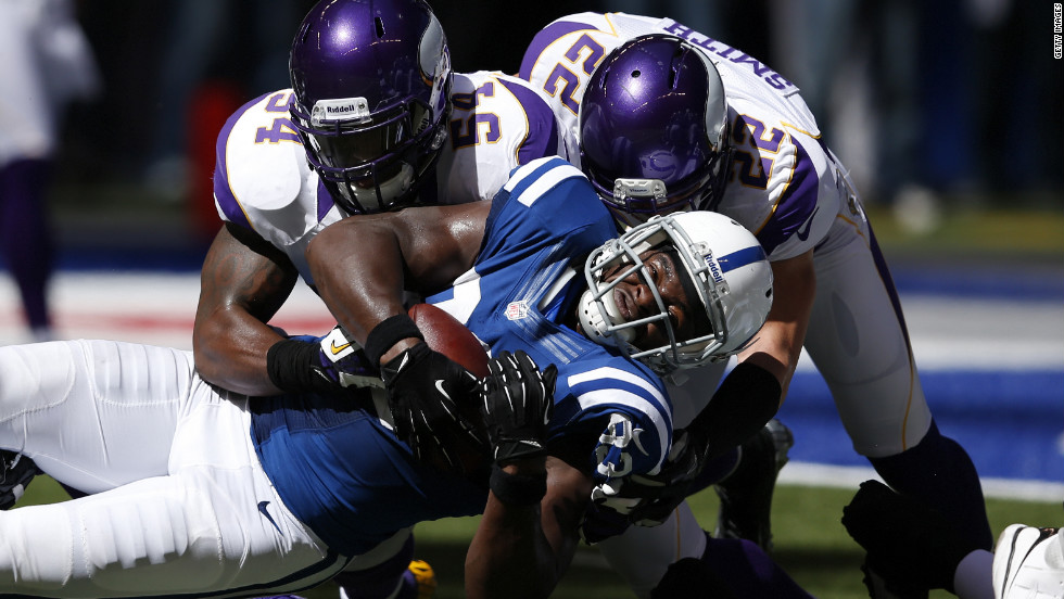 Jasper Brinkley, left, and Harrison Smith of the Minnesota Vikings tackle tight end Dwayne Allen of the Indianapolis Colts during the first half of Sunday's game.