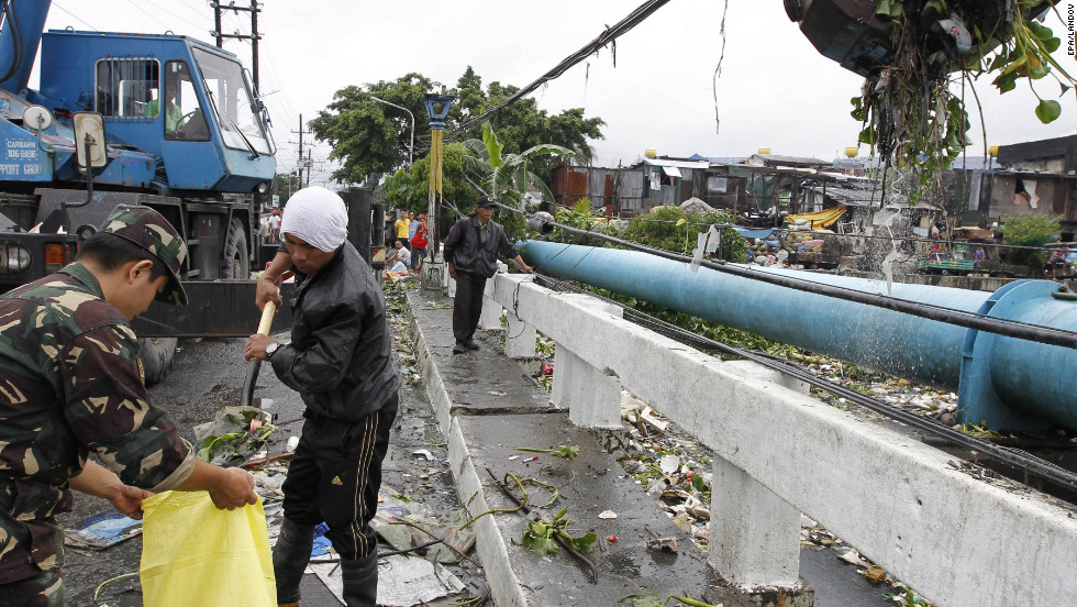Filipinos collect debris that clogs waterways and causes flooding in riverside communities in Malabon City, Philippines, on Sunday.