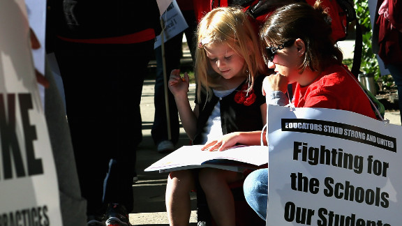 Teacher Jillian Connolly helps her daughter, Mary, study math while picketing outside of William H. Wells Community High School on Monday, September 10.