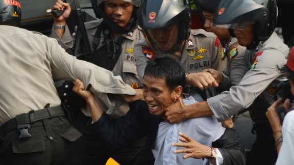 Indonesian anti-riot police arrest a protester Monday outside the U.S. Embassy in Jakarta. Monday
