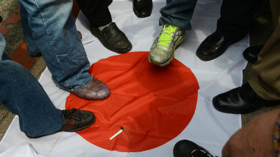 Anti-Japan activists step on a Japanese flag on September 18 during a protest in front of the parliament building in Taipei to demand the Taiwan government cooperate with China against Japan.