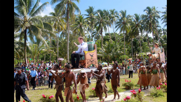 Prince William and Catherine, Duchess of Cambridge, are carried from a boat to their plane Tuesday in Honiara, Guadalcanal Island in the Solomon Islands as they continue their tour of the Far East.
