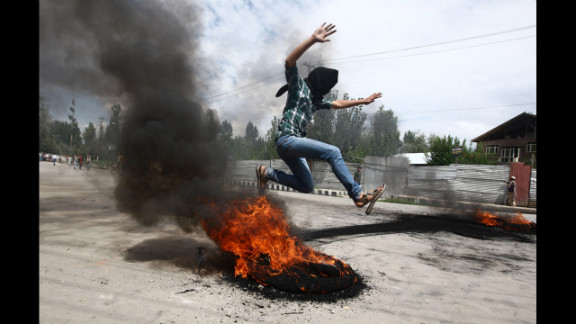 A Kashmiri Muslim boy jumps over a burning tire set up as a roadblock during Tuesday