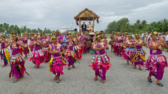 The royal couple are carried from their plane to a welcoming ceremony in Tuvalu on Tuesday.