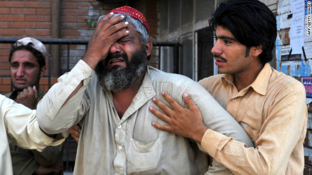 A Pakistani man comforts a mourner at a hospital following a bomb explosion in Peshawar on September 19, 2012.