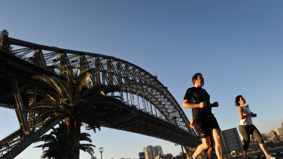 People jog along the Sydney Harbour with the Sydney Harbour bridge seen in the background. ROMEO GACAD/AFP/GettyImages)