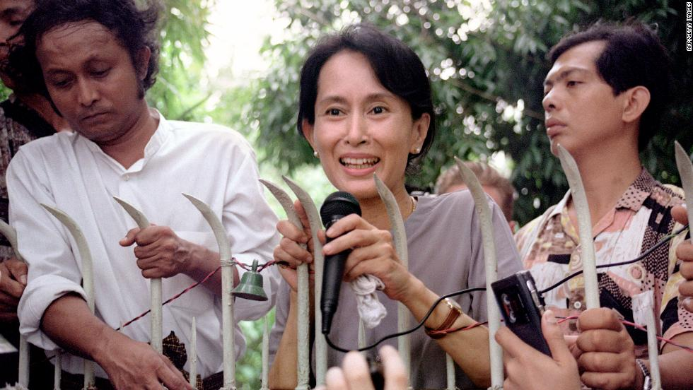 Suu Kyi addresses hundreds of anxious Burmese supporters from the main gate of her family compound in Yangon on July 14, 1995.