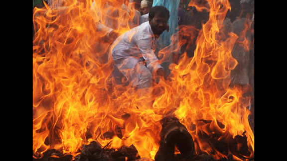 An Indian Muslim student hits a burning effigy of U.S. President Barack Obama during a protest in Kolkata on Wednesday.