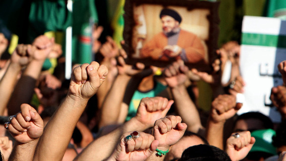 "Supporters of Hezbollah hold a picture depicting Hezbollah leader Hassan Nasrallah and chant the slogan ""God is Great"" during a mass rally in Tyre, Lebanon, on Wednesday. Thousands of Lebanon"