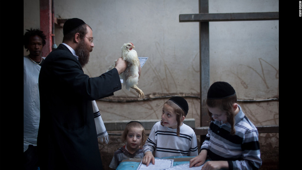 An Ultra-Orthodox Jewish man swings a chicken over his family during the Kaparot ceremony on Thursday in Bnei Brak, Israel. The Jewish ritual is meant to transfer the sins of the past year to the chicken. It is performed before the Day of Atonement, or Yom Kippur, the most important day in the Jewish calendar, which this year will start at sunset on September 25.