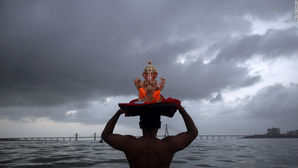 A devotee carries a statue of the Hindu god Ganesh, the deity of prosperity, into the Arabian Sea on the first day of the 10-day Ganesh Chaturthi festival in Mumbai, India, on Thursday. Ganesh idols are taken through the streets in a dancing and singing procession to a river or the sea, where they are immersed to symbolize seeing off the god to take away the misfortunes of all mankind.