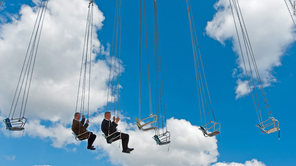 Munich Mayor Christian Ude, left, and Oktoberfest Director Dieter Reiter take a ride on a flying swing during a tour of the Oktoberfest grounds in Munich, Germany, on Thursday, September 20. The world's largest fair runs from September 22 to October 7.