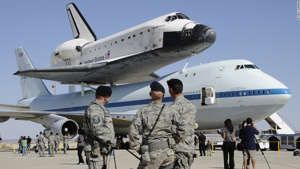 Military personnel look at Endeavour atop the modified Boeing 747 at Edwards Air Force Base on Thursday. Endeavour, along with space shuttles Discovery, Enterprise and Atlantis, became a museum piece after NASA ended its 30-year shuttle program in July 2011.