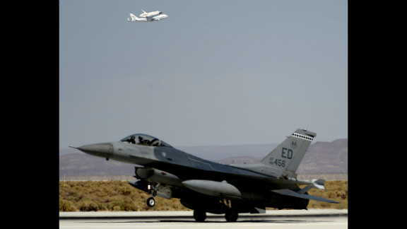 An F-16 fighter jet is seen in the foreground as Endeavour makes a flyby Thursday before landing at Edwards Air Force Base.
