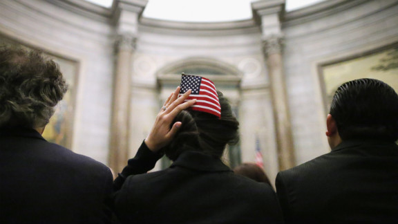 A native of Lebanon, Mirna Mumm uses a U.S. flag to hold her hair in place after becoming one of 215 new citizens during a ceremony at the National Archives on Monday in Washington. The ceremony was held on the 225th anniversary of the signing of the U.S. Constitution.