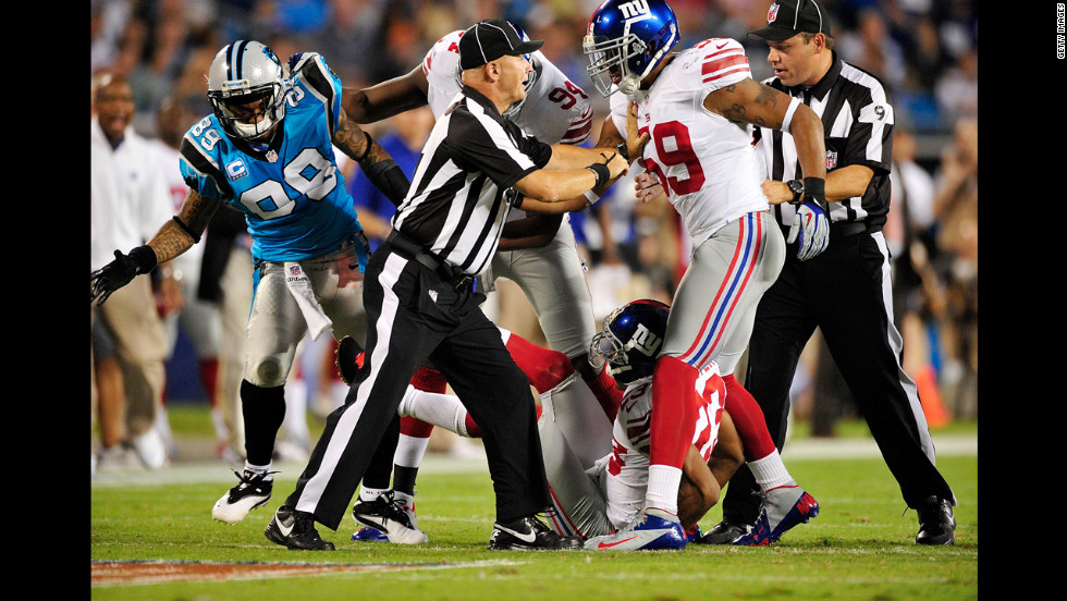 Officials separate the Giants' Michael Boley from the Panthers' Steve Smith as they scuffle after a play.