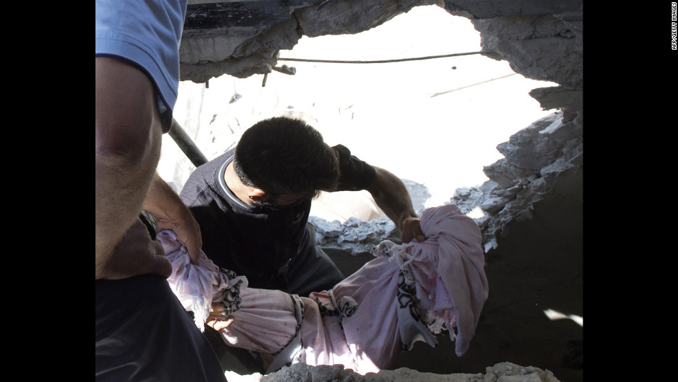 Men carry the covered body of a child killed in an attack by Syrian government forces in Aleppo on Friday.