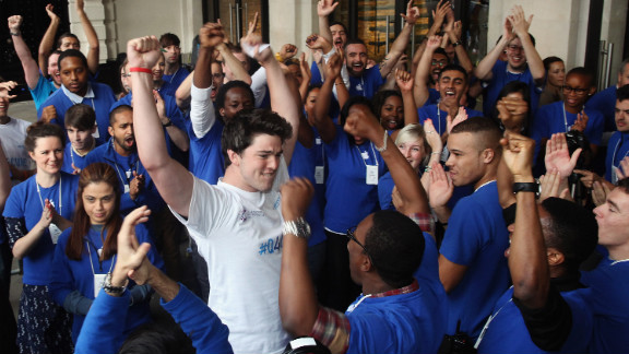 Ryan Williams, 22, of Kent, is cheered by Apple employees as he is let into the Apple Store in London, becoming the first to purchase the iPhone 5 smartphone in London on Friday.