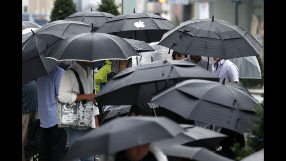 Customers hold umbrellas as they wait in line in Tokyo.