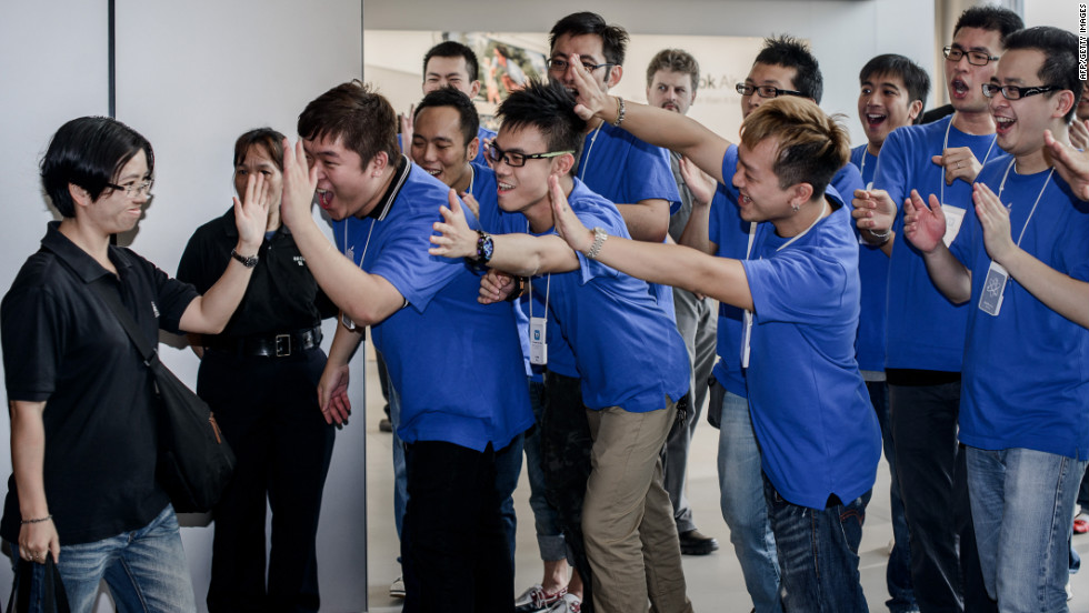 A customer, left, is greeted by employees as she enters the Hong Kong Apple store.