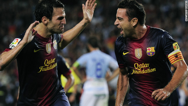 Xavi Hernandez is congratulated by Cesc Fabregas (left) after scoring the opener against Granada in the Camp Nou.