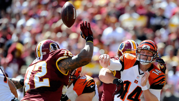 Bengals quarterback Andy Dalton is hit as he throws a pass. The Redskins