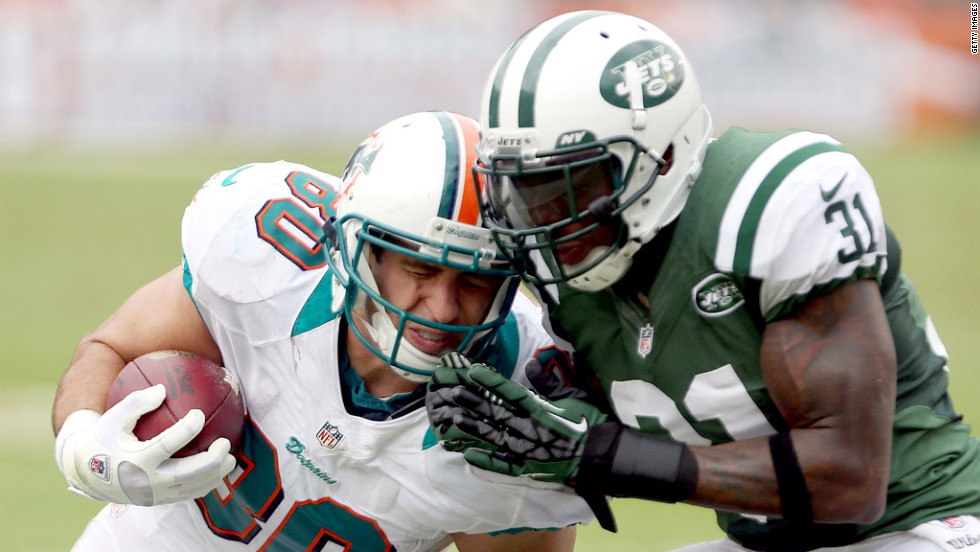 Anthony Fasano of the Miami Dolphins is tackled by Antonio Cromartie of the New York Jets at Sun Life Stadium in Miami Gardens, Florida.