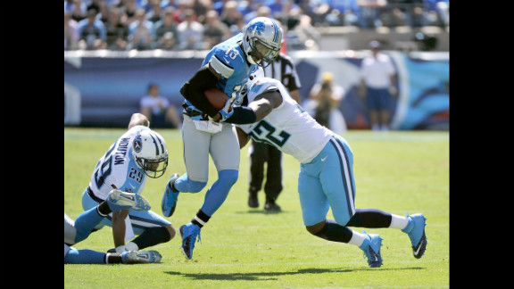 Nate Burleson of the Detroit Lions is tackled by Will Witherspoon of the Tennessee Titans on Sunday in Nashville.