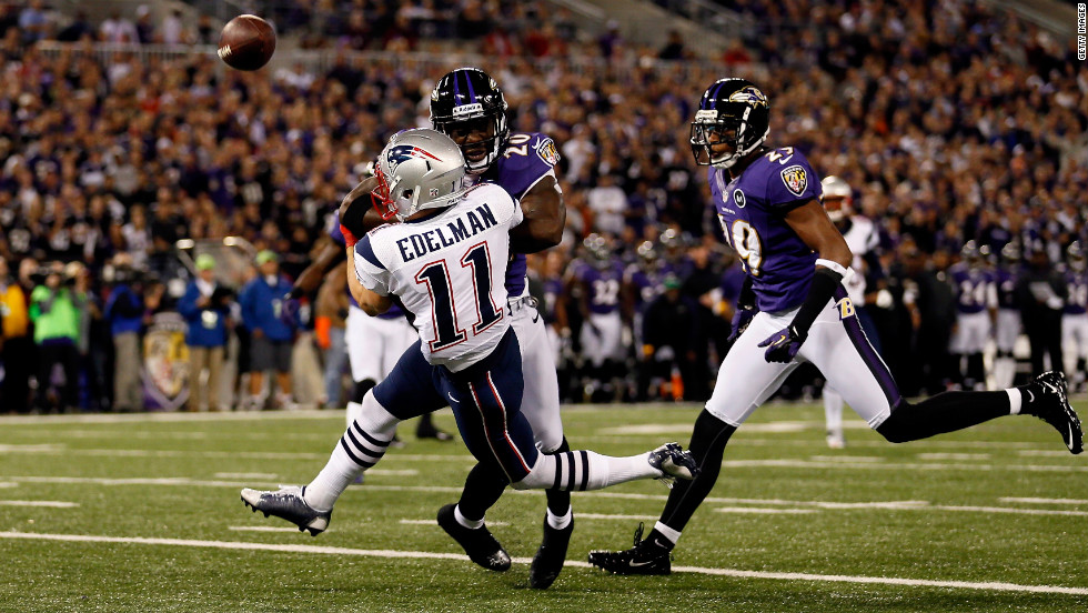 Ed Reed of the Ravens breaks up a pass as he hits the Patriots' Julian Edelman in the first quarter.