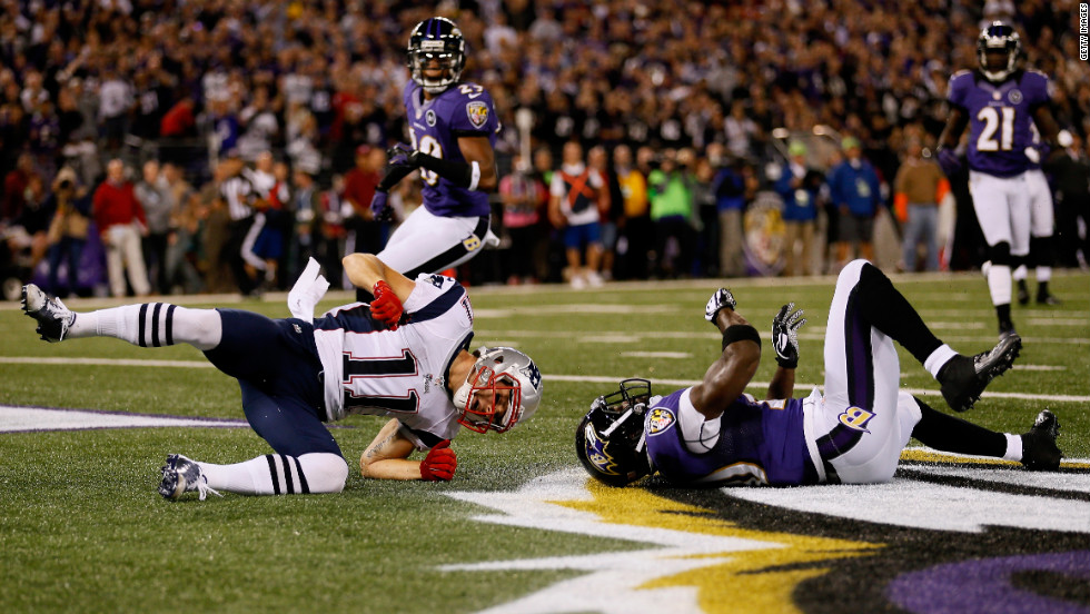 New England's Julian Edelman falls to the turf after taking a hit from Baltimore's Ed Reed.