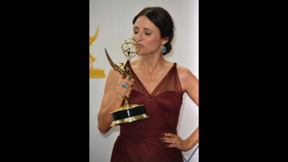 """Julia Louis-Dreyfus of """"Veep"""" kisses her trophy for best lead actress in a comedy."""