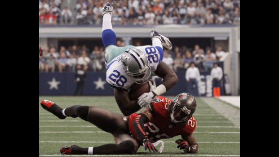 Felix Jones of the Dallas Cowboys is tripped up by D.J. Ware of the Tampa Bay Buccaneers on Sunday in Arlington, Texas.