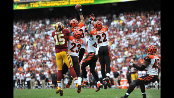 Bengals and Redskins players leap for the ball.