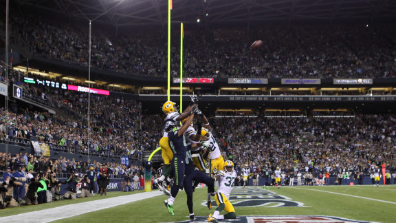 Seahawks wide receiver Golden Tate, in navy blue, jumps for the ball, surrounded by Green Bay players. Before he made the catch in the end zone, Tate shoved Packers defender Sam Shields in the back, which would typically draw an offensive pass interference penalty.