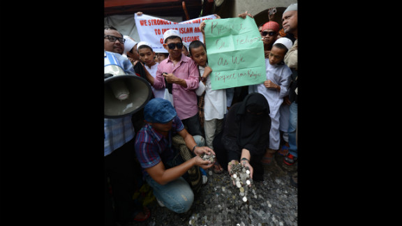 "Philippine Muslims gather coins they collected from the provinces to be used to pay for filing a petition before the Philippine Supreme Court in Manila on Monday asking for local authorities to ban the controversial ""Innocence of Muslims"" film from being posted on the Internet.  Hundreds of Muslim protesters in the Philippines called for a ban on the film before the U.S. Embassy."