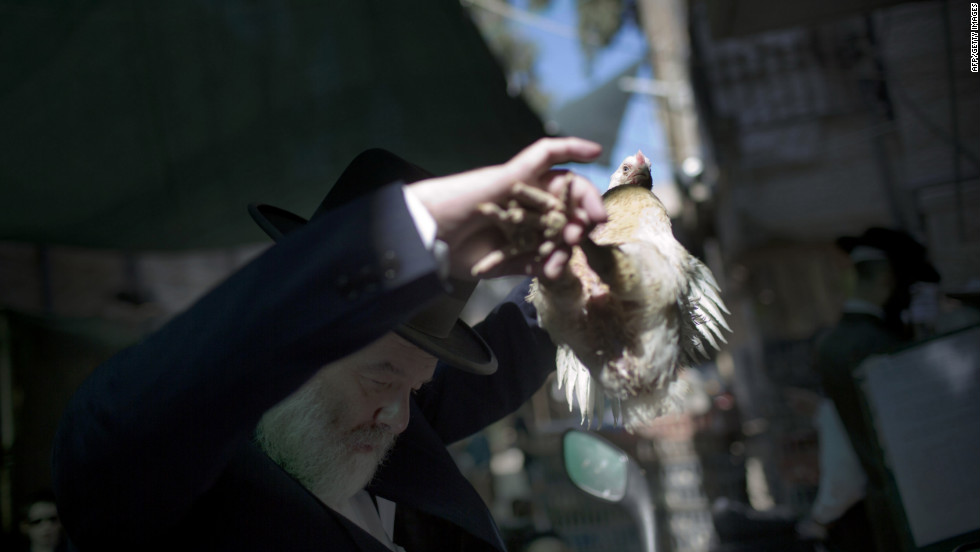 An Ultra-Orthodox Jewish man swings a chicken over his head during the Kaparot ceremony in the Mea Shearim neighborhood of Jerusalem on Sunday.