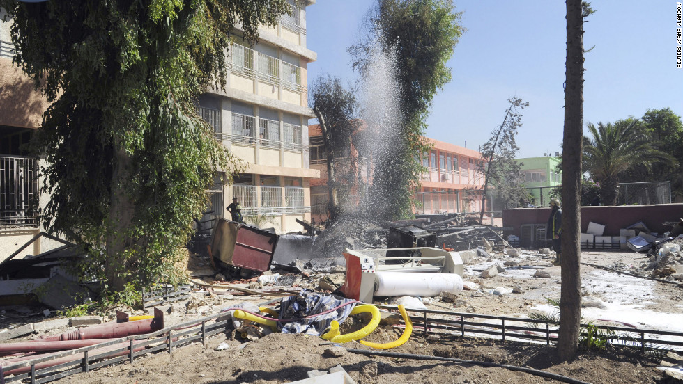 Firefighters stand among debris from the destroyed school building in Damascus on Tuesday.